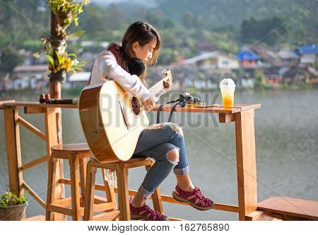 Young woman playing acoustic guitar near the nature