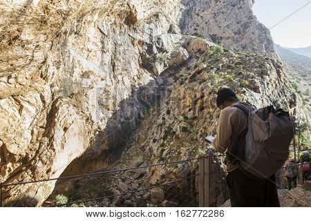 Trekker young man looking up a map at Caminito del Rey path Malaga Spain