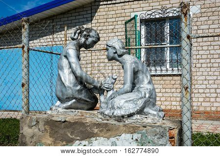 Old Sculpture Of Two Girls.