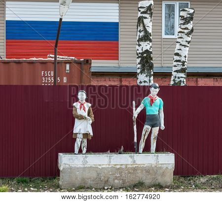 Old Sculptures Of A Boy And Girl In A Pioneer Tie.