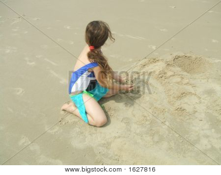 Girl On The Beach Playing With The Sand