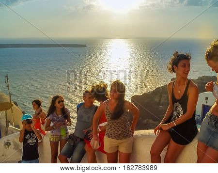 Tourists Enjoying Amazing Sunset View In Oia Village At Santorini