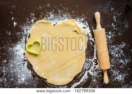 Roll out the dough on a black table. The dough is squeezed out in the shape of a heart for the love of cookies
