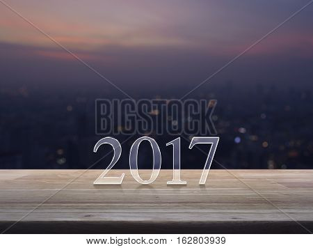 Happy new year 2017 text on wooden table over blur aerial view of cityscape on warm light sundown
