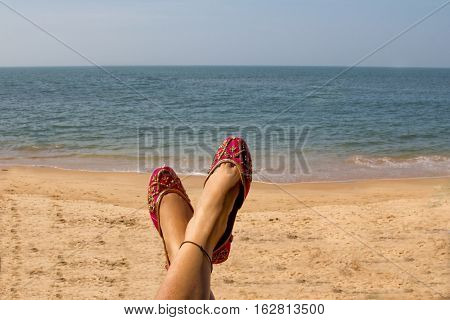 A lady wearing a pair of traditional Indian women's shoes (jutis) at the Anjuna beach in north Goa, India