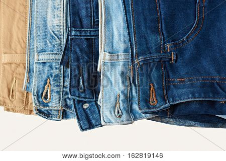 Pile of colorful blue jeans close up isolated on white background