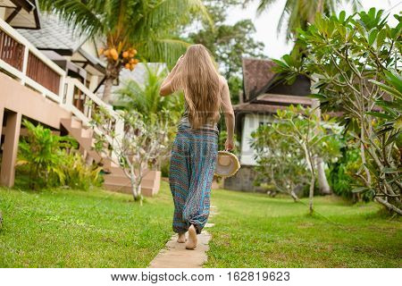 Blonde girl with long hair goes in a green tropical garden
