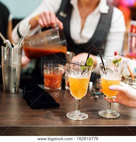 Barman show. Female bartender is making cocktail at night club