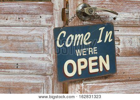 Come In We're Open on the wooden door retro style.