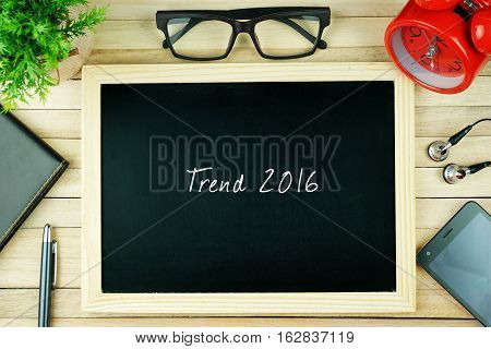 Top view of earphone, calculator, alarm clock, spectacle, notebook, pen, smartphone and chalkboard written with TREND 2016.