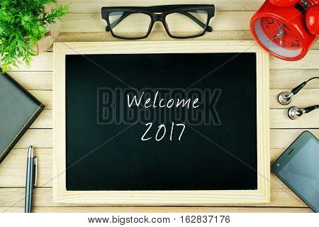 Top view of earphone, calculator, alarm clock, spectacle, notebook, pen, smartphone and chalkboard written with WELCOME 2017.
