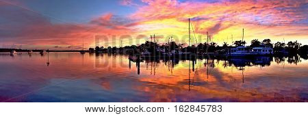 Colorful orange and gold Sunrise silhouette with water reflections Photograph taken at Tin Can Bay, Queensland, Australia,