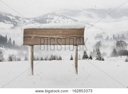 Wide wooden signpost with less snow on it and snowfall and mountains on background