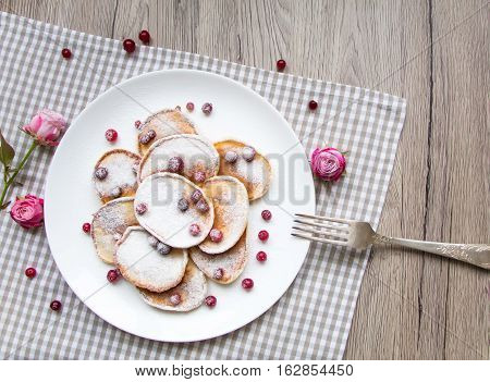 Home made pancakes with cranberries and sugar powder on a white plate. Wooden table rustic decoration berries pink roses and a fork. Top view flat lay view from above