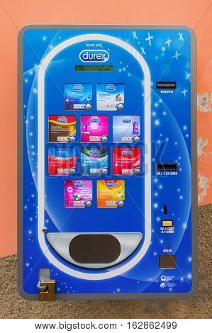 Riomaggiore Italy - July 02 2016: condom machine at a wall. Condom machines are often placed in public toilets subway stations airports or schools as a public health measure to promote safe sex.