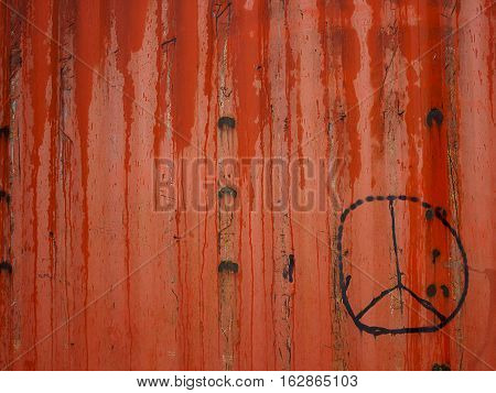 Sign pacifist painted in black on a red fence