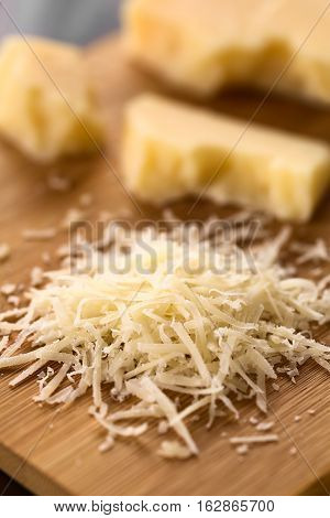 Freshly grated parmesan-like hard cheese on wooden board with cheese pieces in the back photographed with natural light (Selective Focus Focus one third into the image)