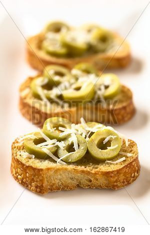Crostini with green olive slices and freshly grated parmesan-like hard cheese photographed with natural light (Selective Focus Focus in the middle of the first crostini)