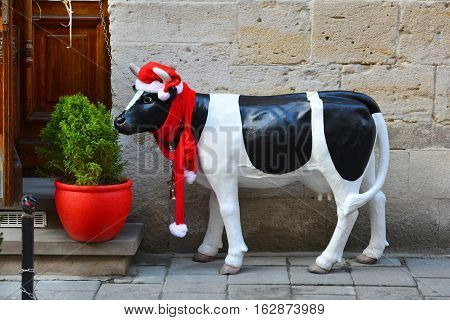 Christmas figurine of a spotted cow in a red hat and red scarf. New Year decorations.
