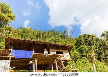 Happy woman dangle her legs with smiling face on a small thatched cottage in Ban Pa Pong Piang Chiang Mai province Thailand