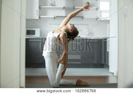 Sporty attractive woman practicing yoga, sitting in Camel exercise, Ustrasana pose , working out, wearing white sportswear, indoor full length, home interior background