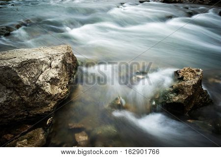 Water flowing by some rocks in a cascading stream in Missouri. Long exposure was used to give the water a blurred silky look.