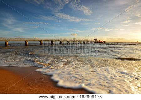 Beautiful scenery of sunset sky at beach with wave motion at foreground and long jetty at background. Motion blur on the foreground due to slow or fast shutter speed shot. Composition of nature.