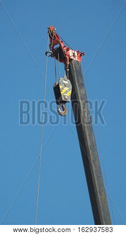 Close-up to hook of crane truck and blue sky background