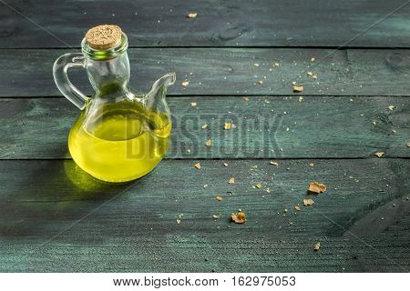 A candid photo of a pitcher of olive oil on a wooden board with bread crumbs and copyspace