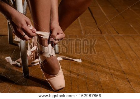 Ballerina Tying Ballet Shoes Sitting On The Stage
