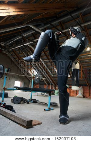 The athlete fulfills a kick in the gym