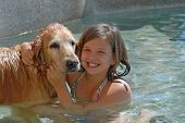 image of swimming pool family  - young girl swimming in pool with her pet a golden retreiver in pool