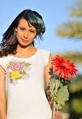 image of senorita  - Beautiful young woman holding red flower - JPG