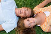 image of teenage boys  - happy teenage boy and girl laying on grass - JPG