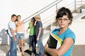 stock photo of school bullying  - outcast sad girl at university with group of friends behind - JPG