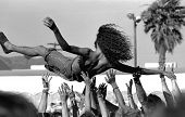 stock photo of kinda  - cool kinda grainy shot of a guy crowd surfing at dead concert