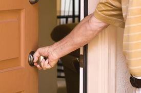 image of front door  - Man opening the front door of his home saying  - JPG