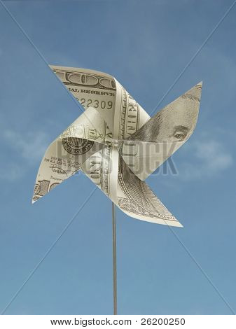 Toy windmill cut out from 100 US banknote over blue sky