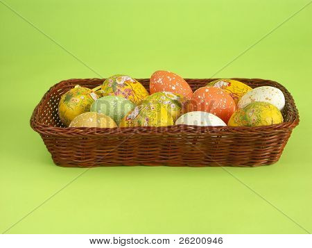 Wicker basket with Easter eggs over light green background