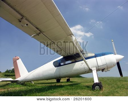 Highwing monoplane parked on grass field