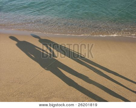 Long shadow of young couple holding hands cast on beach sand