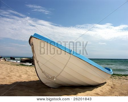 Fisherman's boat made fast nearshore on sandy beach