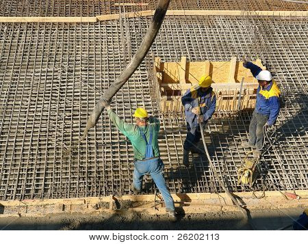 Three construction workers pouring concrete mix into reinforced structure at the building site