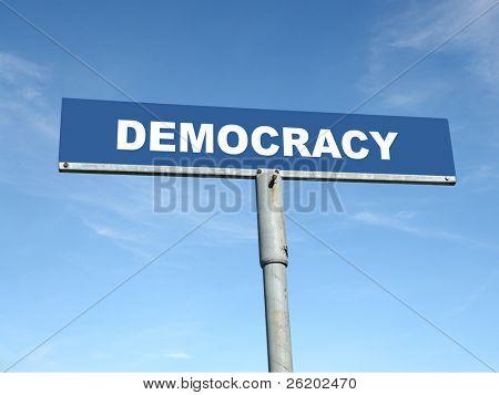 Metal signpost spelling Democracy over blue sky