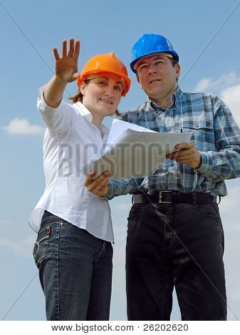 Young couple wearing helmets visualizing their new future house based on their building project documentation