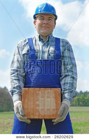 Construction worker in blue jumpsuit and helmet holding hollow brick