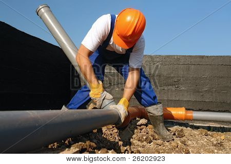 Plumber assembling pvc sewage pipes in house foundation