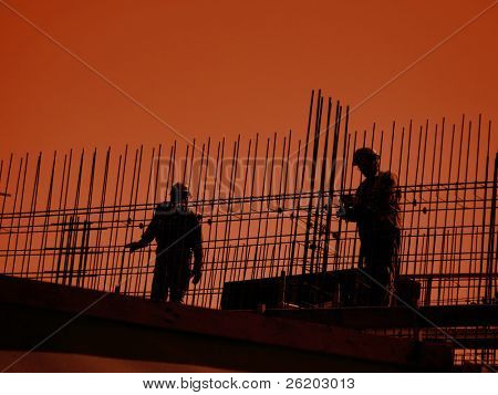 Silhouettes of construction workers working with steel reinforcement against orange sky