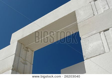 Prefabricated aerated autoclaved concrete lintel placed on house wall blocks shot over blue sky