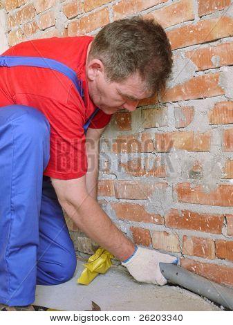 Plumber installing pvc sewage pipe inside unfinished house